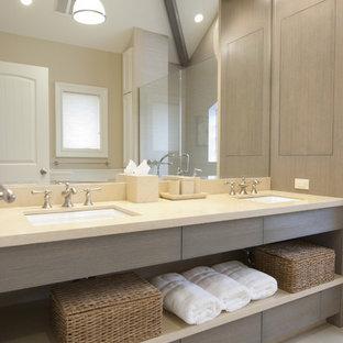 Diseño de cuarto de baño principal, actual, de tamaño medio, con lavabo bajoencimera, puertas de armario grises y encimera de piedra caliza