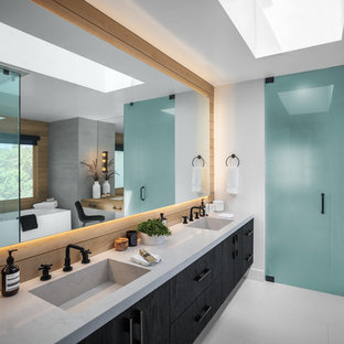 This is an example of a large contemporary master bathroom in Los Angeles with flat-panel cabinets, black cabinets, gray tile, white walls, vinyl floors, marble benchtops, white floor, grey benchtops, an integrated sink, a freestanding tub, a corner shower, a one-piece toilet, a hinged shower door and cement tile.