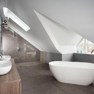 Cette photo montre une salle de bain principale tendance avec une vasque, une baignoire indépendante, une douche à l'italienne, un mur gris et un sol marron.