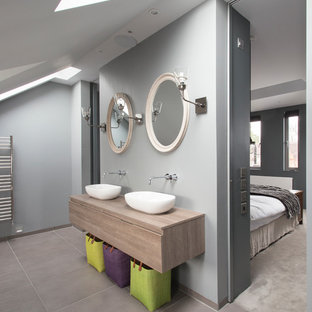 Photo of a contemporary ensuite bathroom in London with a vessel sink, flat-panel cabinets and grey walls.