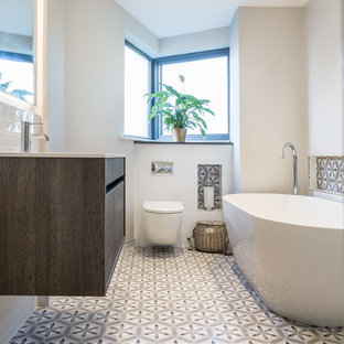 Medium sized contemporary bathroom in Dublin with flat-panel cabinets, dark wood cabinets, a freestanding bath, a wall mounted toilet, white walls, multi-coloured floors, multi-coloured tiles, cement tiles and cement flooring.
