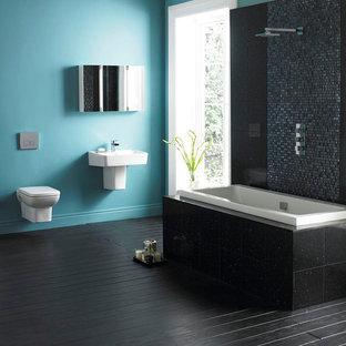 Idée de décoration pour une salle de bain design avec un lavabo suspendu, une baignoire posée, un combiné douche/baignoire, un WC suspendu, un carrelage noir, un mur bleu et un sol en bois peint.