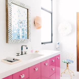 Inredning av ett modernt badrum, med vita väggar, ett integrerad handfat, släta luckor och röda skåp
