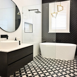 Photo of a mid-sized contemporary master bathroom in Brisbane with flat-panel cabinets, dark wood cabinets, a freestanding tub, an open shower, black tile, white tile, white walls, a vessel sink, multi-coloured floor, an open shower and beige benchtops.