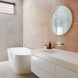 Esempio di una stanza da bagno contemporanea di medie dimensioni con ante lisce, ante bianche, vasca freestanding, pareti multicolore e piastrelle arancioni