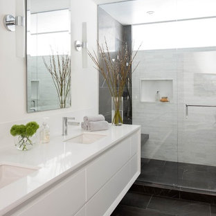 Inspiration for a contemporary bathroom in Los Angeles with engineered quartz benchtops, flat-panel cabinets, white cabinets, an alcove shower, white tile, white walls and an undermount sink.