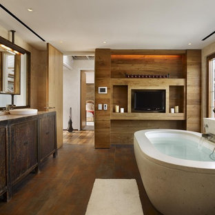 Example of a trendy brown floor bathroom design in New York with a vessel sink, furniture-like cabinets, distressed cabinets, wood countertops and an undermount tub