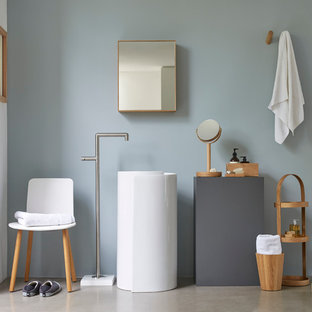 This is an example of a scandinavian bathroom in London with open cabinets, medium wood cabinets, grey walls, concrete flooring and a pedestal sink.