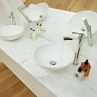 Inspiration for a contemporary family bathroom in London with a vessel sink, flat-panel cabinets, a freestanding bath, an alcove shower and white walls.