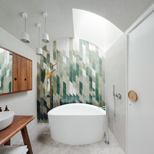 Large trendy green tile beige floor freestanding bathtub photo in Sydney with a vessel sink and medium tone wood cabinets