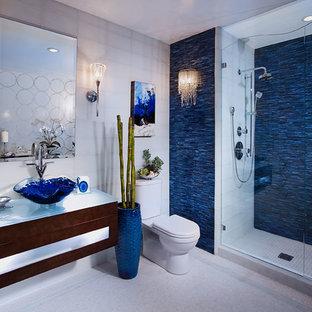 Неиссякаемый источник вдохновения для домашнего уюта: главная ванная комната среднего размера в современном стиле с плоскими фасадами, темными деревянными фасадами, душем в нише, раздельным унитазом, серыми стенами, полом из мозаичной плитки, настольной раковиной, стеклянной столешницей, белым полом, душем с распашными дверями, синей плиткой, стеклянной плиткой и белой столешницей