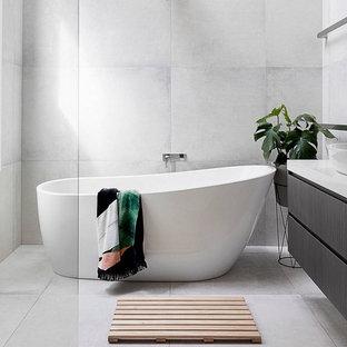 Imagen de cuarto de baño actual con armarios con paneles lisos, puertas de armario negras, bañera exenta, baldosas y/o azulejos grises, paredes grises, lavabo sobreencimera, suelo gris, encimeras blancas, baldosas y/o azulejos de porcelana y suelo de baldosas de porcelana