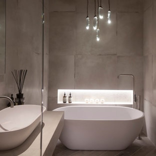This is an example of a medium sized contemporary ensuite bathroom in Cheshire with a trough sink, freestanding cabinets, distressed cabinets, a freestanding bath, a shower/bath combination, a wall mounted toilet, white tiles, porcelain tiles, white walls and porcelain flooring.