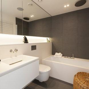 Foto de cuarto de baño infantil, contemporáneo, de tamaño medio, con lavabo suspendido, armarios tipo mueble, puertas de armario blancas, encimera de acrílico, bañera esquinera, sanitario de pared, baldosas y/o azulejos grises, baldosas y/o azulejos de piedra, paredes blancas y suelo de pizarra