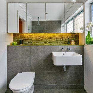 Design ideas for a contemporary bathroom in Sydney with a one-piece toilet, gray tile, a wall-mount sink, grey floor and a single vanity.
