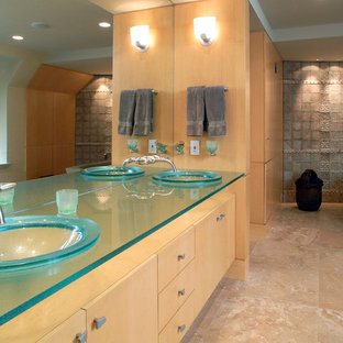 Design ideas for a contemporary bathroom in Philadelphia with a vessel sink, flat-panel cabinets, medium wood cabinets, glass worktops, a freestanding bath, beige tiles and blue worktops.