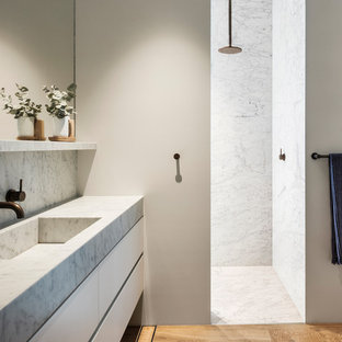This is an example of a contemporary bathroom in Sydney with flat-panel cabinets, white cabinets, a curbless shower, white tile, white walls, medium hardwood floors, an integrated sink, brown floor, an open shower and white benchtops.