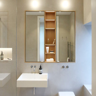 This is an example of a small contemporary ensuite bathroom in London with a corner shower, a wall mounted toilet, grey tiles, porcelain tiles, porcelain flooring, a wall-mounted sink and grey floors.