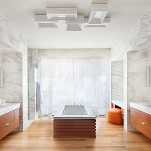 Example of a large trendy master white tile and stone tile light wood floor and beige floor corner shower design in Los Angeles with flat-panel cabinets, medium tone wood cabinets, an undermount tub, an undermount sink, white walls and solid surface countertops