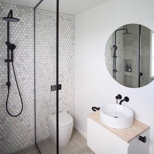На фото: ванная комната в современном стиле с плоскими фасадами, белыми фасадами, душевой комнатой, унитазом-моноблоком, серой плиткой, плиткой мозаикой, серыми стенами, бетонным полом, душевой кабиной, настольной раковиной, столешницей из дерева, серым полом, открытым душем и бежевой столешницей с