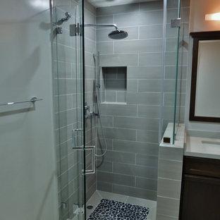Inredning av ett modernt litet badrum med dusch, med ett undermonterad handfat, luckor med infälld panel, skåp i mörkt trä, bänkskiva i kvarts, en hörndusch, en toalettstol med hel cisternkåpa, grå kakel, porslinskakel, grå väggar och klinkergolv i porslin