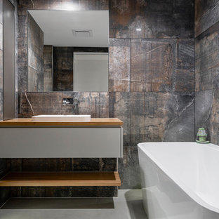 Design ideas for a contemporary bathroom in Sunshine Coast with flat-panel cabinets, grey cabinets, a freestanding tub, beige tile, black tile, brown tile, gray tile, a drop-in sink, wood benchtops, grey floor and brown benchtops.
