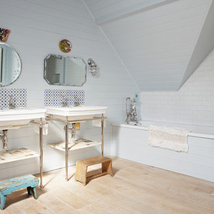 Photo of a contemporary bathroom in London with a console sink, a built-in bath, a shower/bath combination, multi-coloured tiles, white walls and light hardwood flooring.