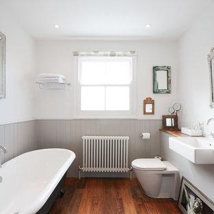На фото: ванная комната среднего размера в викторианском стиле с столешницей из дерева, отдельно стоящей ванной и паркетным полом среднего тона с