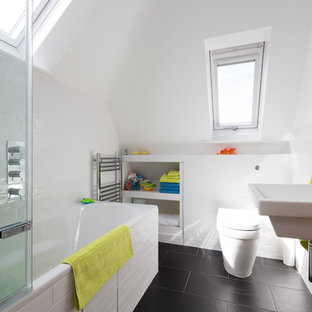 Inspiration for a contemporary kids bathroom in London with a wall-mount sink, open cabinets, white cabinets, a drop-in tub, a shower/bathtub combo, a wall-mount toilet, white tile, white walls and black floor.