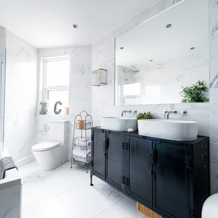 Inspiration for a contemporary master gray tile and marble tile marble floor and gray floor bathroom remodel in San Francisco with recessed-panel cabinets, black cabinets, a one-piece toilet, gray walls and a vessel sink