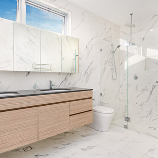 Inspiration for a contemporary master bathroom in Newcastle - Maitland with flat-panel cabinets, light wood cabinets, an alcove shower, a one-piece toilet, white tile, marble floors, an undermount sink, white floor, a hinged shower door and black benchtops.