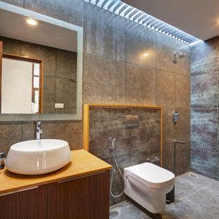 Modernes Duschbad mit flächenbündigen Schrankfronten, hellbraunen Holzschränken, offener Dusche, Wandtoilette, grauen Fliesen, Aufsatzwaschbecken, grauem Boden, offener Dusche und oranger Waschtischplatte in Bangalore