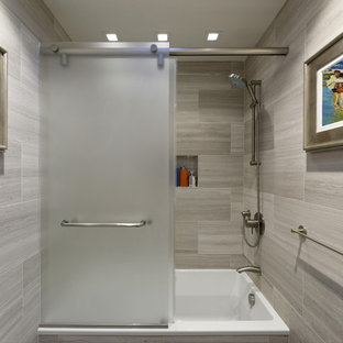 Medium sized contemporary family bathroom in DC Metro with freestanding cabinets, medium wood cabinets, an alcove bath, a shower/bath combination, a wall mounted toilet, grey tiles, marble tiles, grey walls, slate flooring, a vessel sink, limestone worktops, black floors, a sliding door and grey worktops.