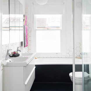 Photo of a contemporary shower room bathroom in London with flat-panel cabinets, white cabinets, an alcove bath, a two-piece toilet, white tiles, white walls, a console sink, black floors and a sliding door.