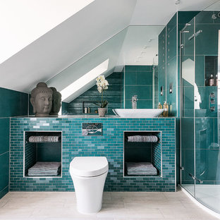 Contemporary bathroom in London with a corner shower, a wall mounted toilet, blue tiles, white walls and a vessel sink.