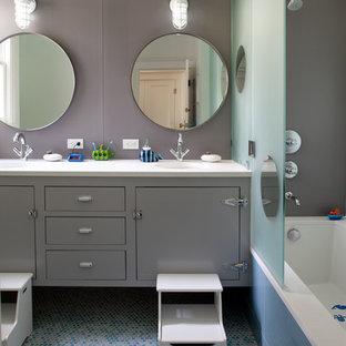 Exemple d'une salle de bain tendance de taille moyenne pour enfant avec des portes de placard grises, un placard à porte plane, un mur gris, un sol en carrelage de terre cuite, une baignoire encastrée, un combiné douche/baignoire, un lavabo encastré, un plan de toilette en stéatite, un sol bleu, une cabine de douche à porte battante, un plan de toilette blanc, meuble double vasque et meuble-lavabo suspendu.