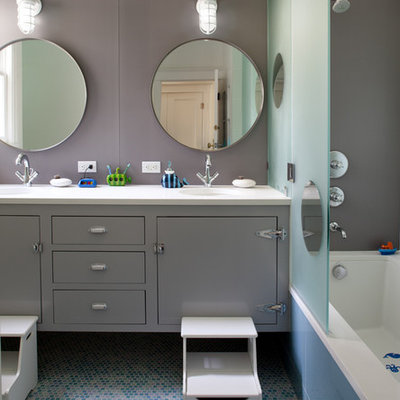Inspiration for a mid-sized contemporary kids' mosaic tile floor, blue floor and double-sink tub/shower combo remodel in San Francisco with gray cabinets, flat-panel cabinets, gray walls, an undermount tub, an undermount sink, soapstone countertops, a hinged shower door, white countertops and a floating vanity