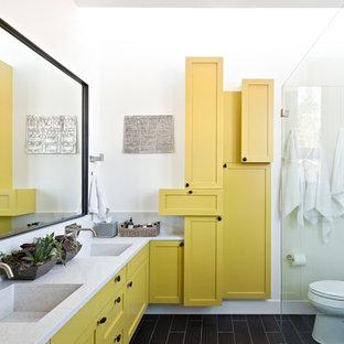 Immagine di una stanza da bagno design con lavabo integrato, ante in stile shaker, ante gialle, doccia a filo pavimento e piastrelle marroni