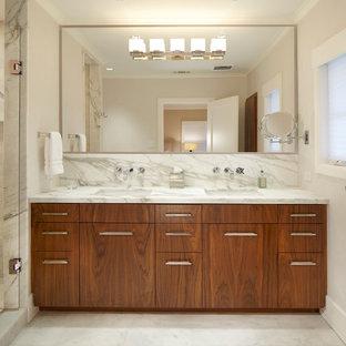 Modelo de cuarto de baño actual con lavabo bajoencimera, armarios con paneles lisos, puertas de armario de madera oscura, encimera de mármol, ducha empotrada, baldosas y/o azulejos blancos y baldosas y/o azulejos de mármol
