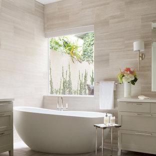 Imagen de cuarto de baño principal, contemporáneo, de tamaño medio, con armarios estilo shaker, puertas de armario grises, encimera de acrílico, bañera exenta, baldosas y/o azulejos beige, losas de piedra y suelo de mármol