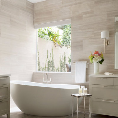 Freestanding bathtub - mid-sized contemporary master beige tile and stone slab marble floor freestanding bathtub idea in Miami with shaker cabinets, gray cabinets and solid surface countertops
