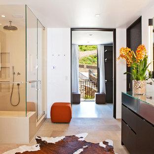 Idee per una grande stanza da bagno design con lavabo sottopiano, ante lisce, ante in legno bruno, top in vetro, doccia ad angolo, WC monopezzo, piastrelle beige, piastrelle in pietra, pareti bianche e pavimento in pietra calcarea