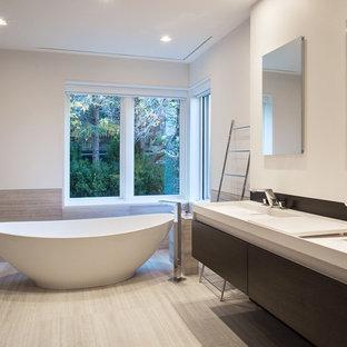 Foto di una grande stanza da bagno padronale minimal con vasca freestanding, piastrelle beige, pareti bianche, doccia ad angolo, ante lisce, ante in legno bruno, pavimento in laminato, lavabo integrato, pavimento beige e porta doccia a battente