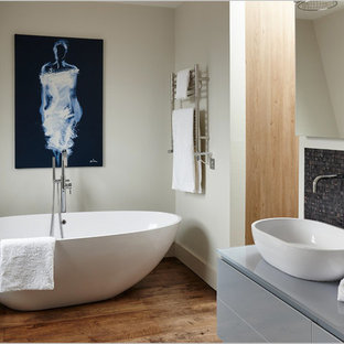 Contemporary bathroom in London with flat-panel cabinets, grey cabinets, a freestanding bath