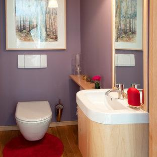 Esempio di una stanza da bagno contemporanea con ante in legno chiaro, WC monopezzo, pareti viola, parquet chiaro e top in superficie solida