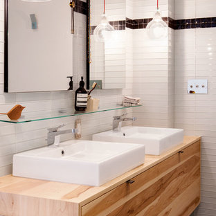 Bathroom - contemporary black tile and white tile white floor bathroom idea in New York with flat-panel cabinets, medium tone wood cabinets, white walls, a vessel sink, wood countertops and brown countertops