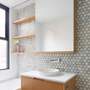 Design ideas for a contemporary bathroom in Sydney with flat-panel cabinets, medium wood cabinets, a drop-in tub, blue tile, gray tile, white tile, mosaic tile, white walls, a vessel sink, brown floor and white benchtops.
