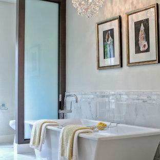 Modelo de cuarto de baño contemporáneo con bañera exenta, baldosas y/o azulejos grises y baldosas y/o azulejos de porcelana