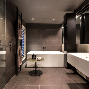 Large trendy master gray tile and ceramic tile ceramic floor bathroom photo in Melbourne with black cabinets, multicolored walls and an integrated sink