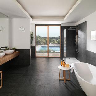 Ispirazione per un'ampia stanza da bagno padronale minimal con vasca freestanding, doccia ad angolo, pareti bianche, lavabo a bacinella, top in legno, piastrelle nere, piastrelle di ciottoli, pavimento in gres porcellanato e pavimento nero